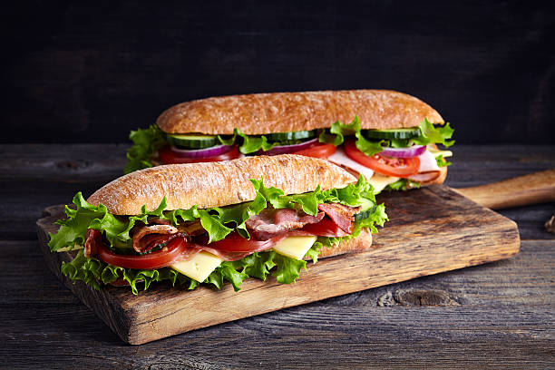 Two fresh submarine sandwiches Two fresh submarine sandwiches with ham, cheese, bacon, tomatoes, lettuce, cucumbers and onions on wooden cutting board submarine sandwich stock pictures, royalty-free photos & images
