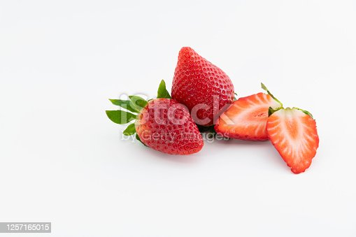 Close up two fresh whole strawberries next to a strawberry cut in half on a light background. Healthy and vegan food concept.