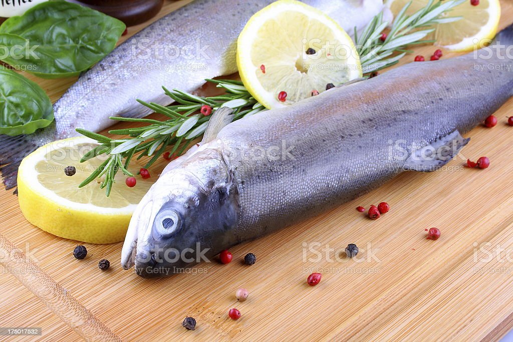 Two fresh whole trout with species on bamboo board royalty-free stock photo