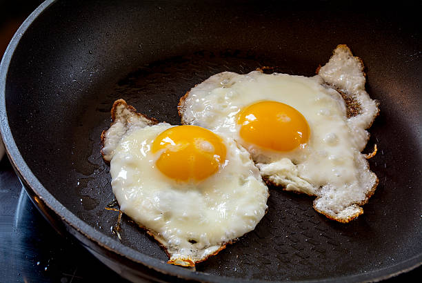 two fried eggs in a black pan - fried egg stock photos and pictures