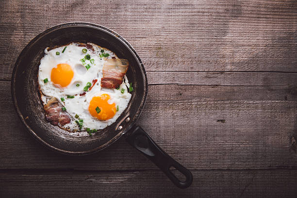 Two fried eggs with bacon and onion stock photo