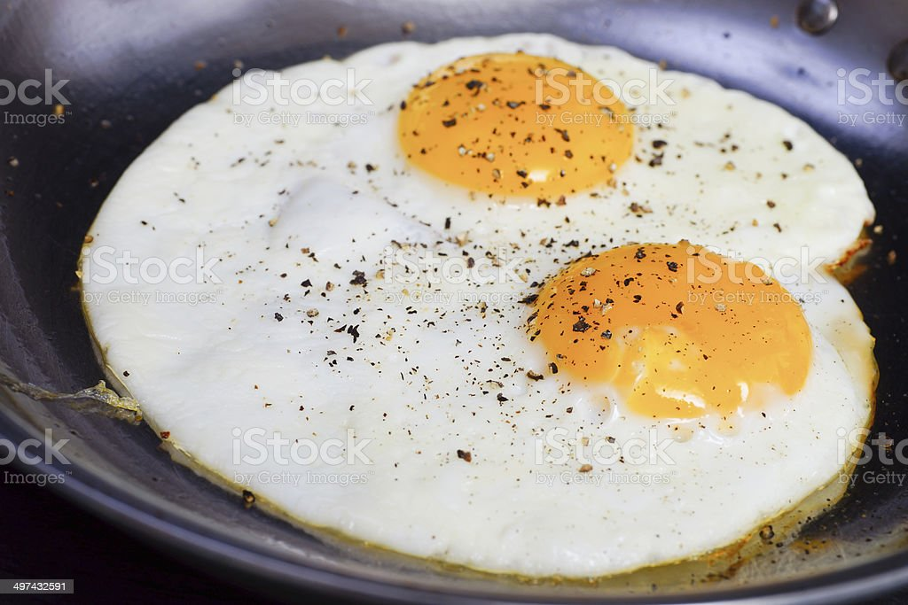 two fried eggs with peppers in a pan stock photo