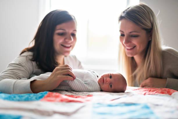 twee vriend meisje met een pasgeboren baby op bed - lesbische stockfoto's en -beelden