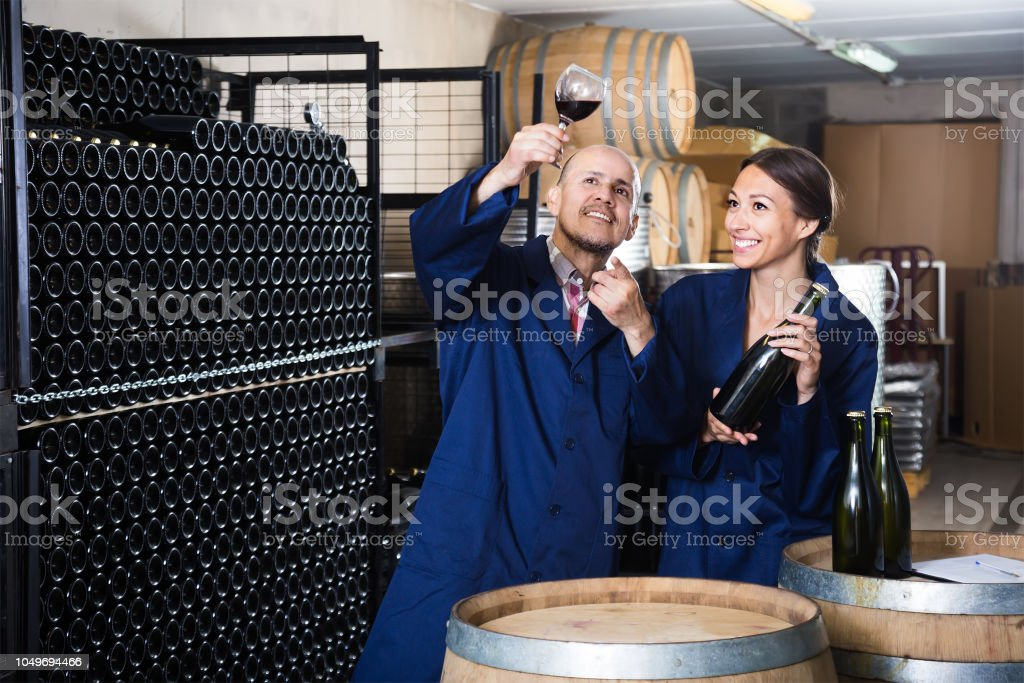 Two friendly winery workers holding glass of wine in aging section of...