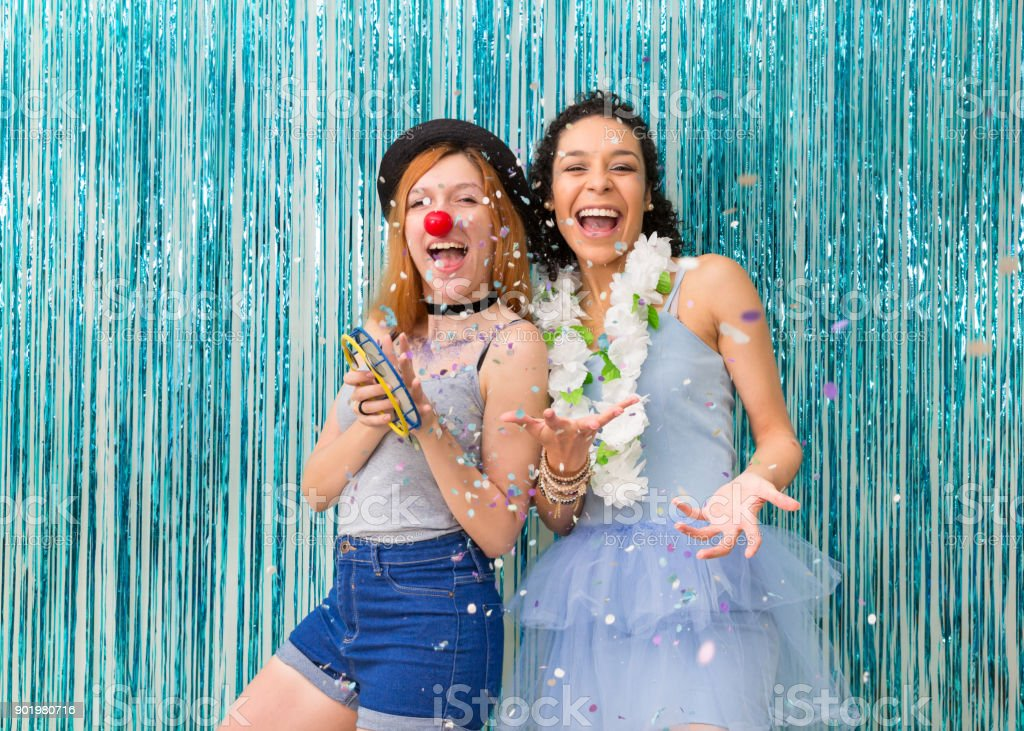 Two friends are celebrating Carnaval. Blue color predominant. Confetti.'n stock photo
