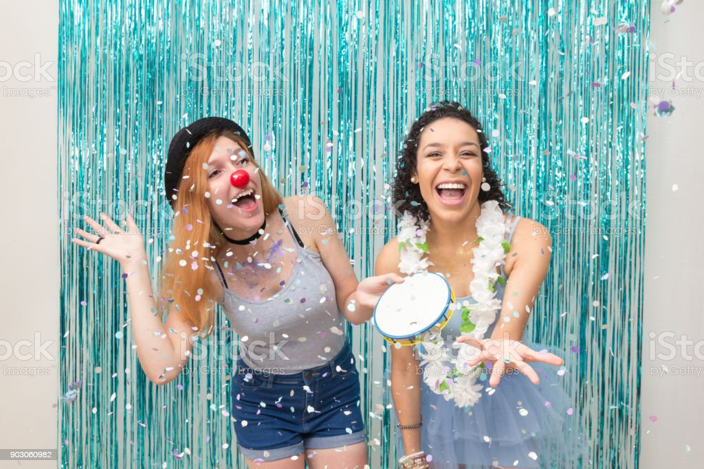 Two friends are celebrating Carnaval. Blue color predominant. Rain of confetti. Tambourine'n stock photo