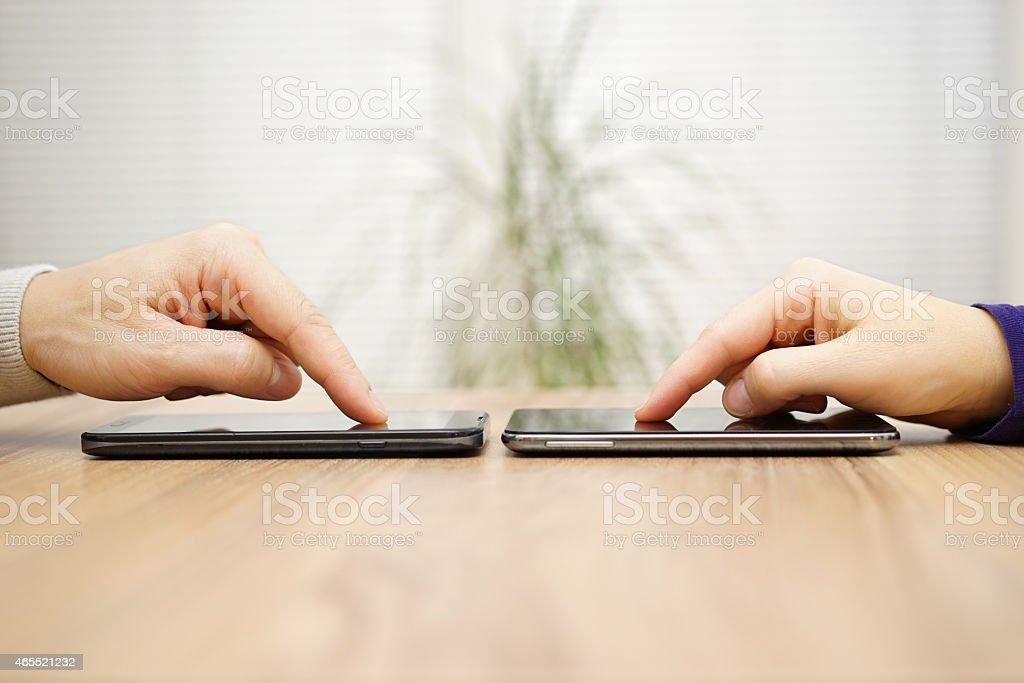 Zwei Freunde mit Verbindungstür und im Dateien über Smartphones – Foto