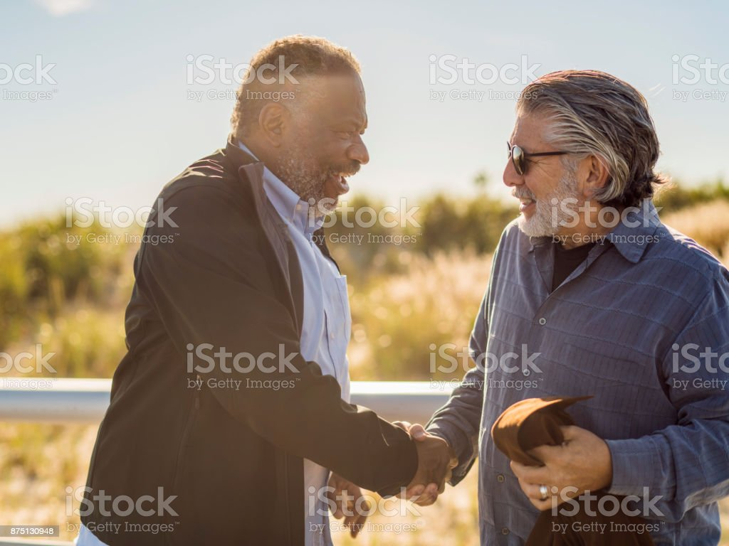 Two friends, Black and White men, meet on the Jones Beach stock photo