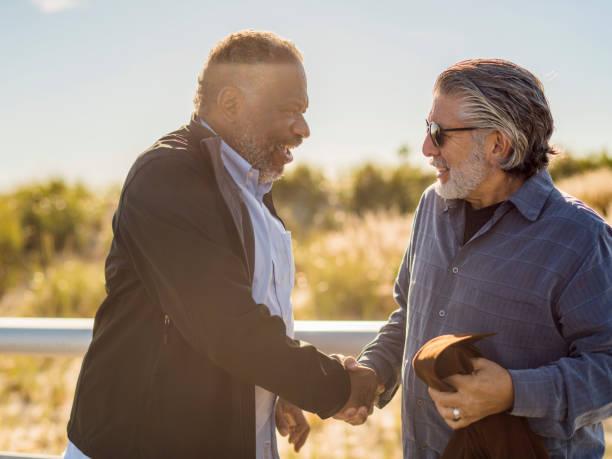 Two friends, Black and White men, meet on the Jones Beach stock photo