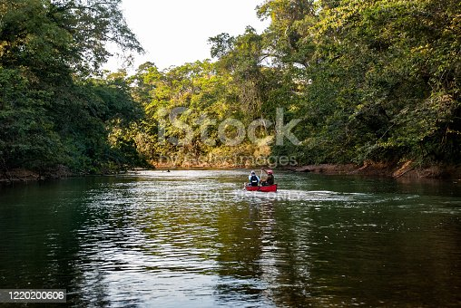 Two friends share a late afternoon canoe trip down the Sibun River in Belize.