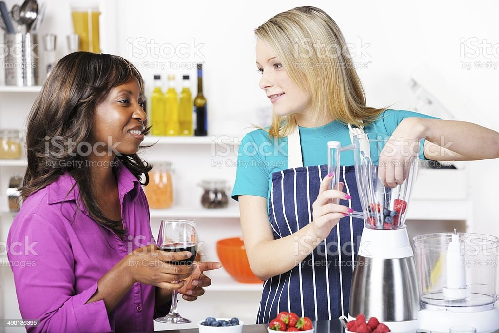 Two Friends Catching-Up While Preparing Healthy  Dessert In A Kitchen royalty-free stock photo
