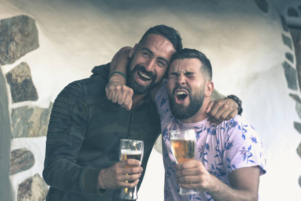 Two friends celebrating with beer stock photo