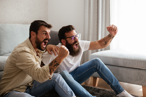 Two young hipsters are watching football mach. It is final minute and score is even, but their favorite club is winning. They are cheering, smiling and hopping for their team to win.