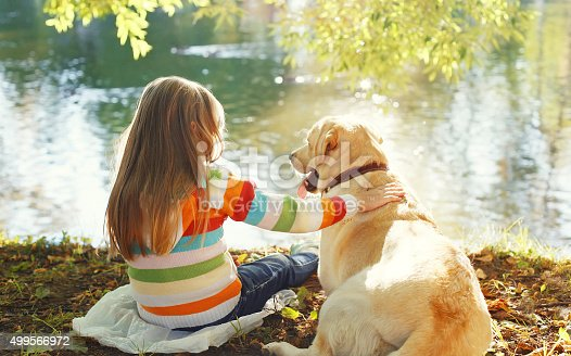istock Two friends, child with Labrador retriever dog sitting in sunny 499566972