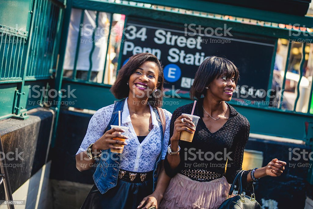 Two friends coming out from the subway stock photo