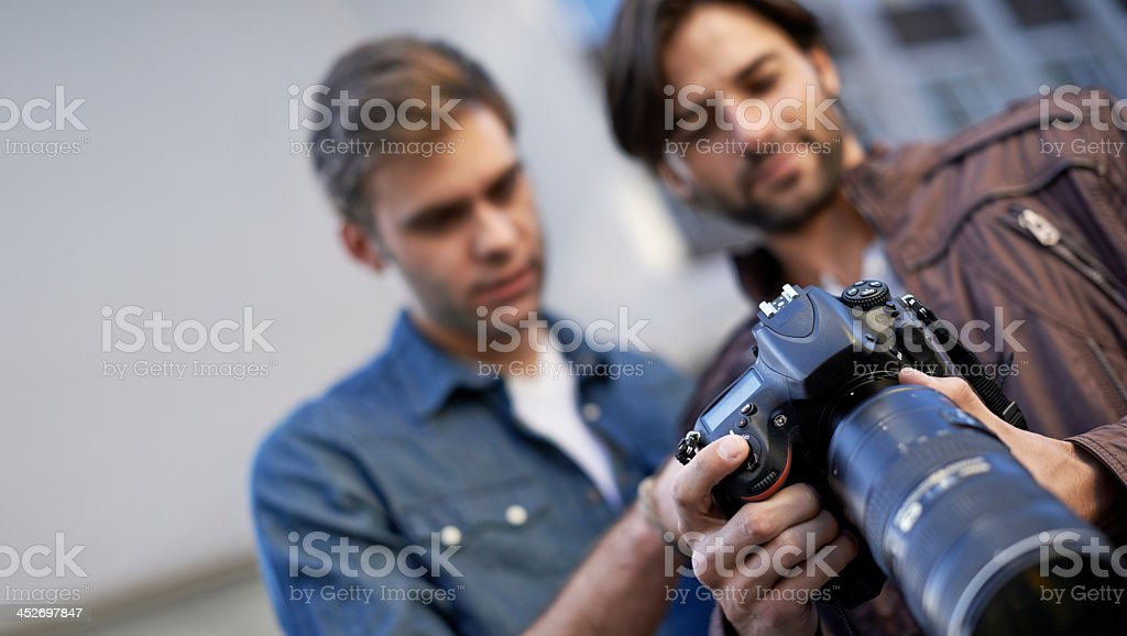 Two friends discussing their photographs stock photo