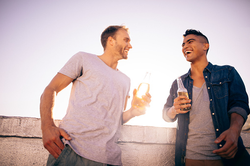 Two friends drinking and laughing on the rooftop at sunset
