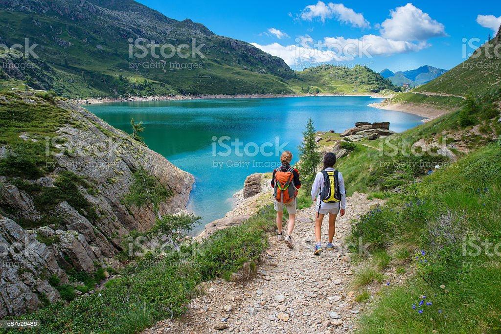 Two friends during a hike in the mountains walking stock photo