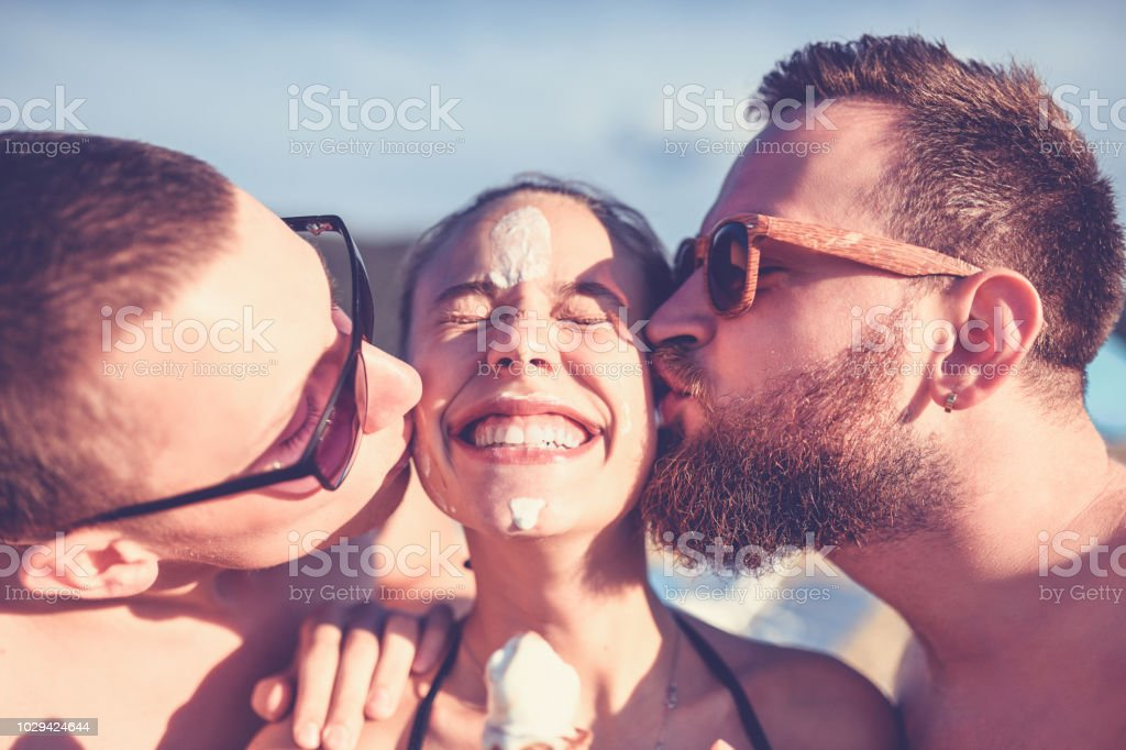 two friends eating ice cream and kissing a girl stock photo more