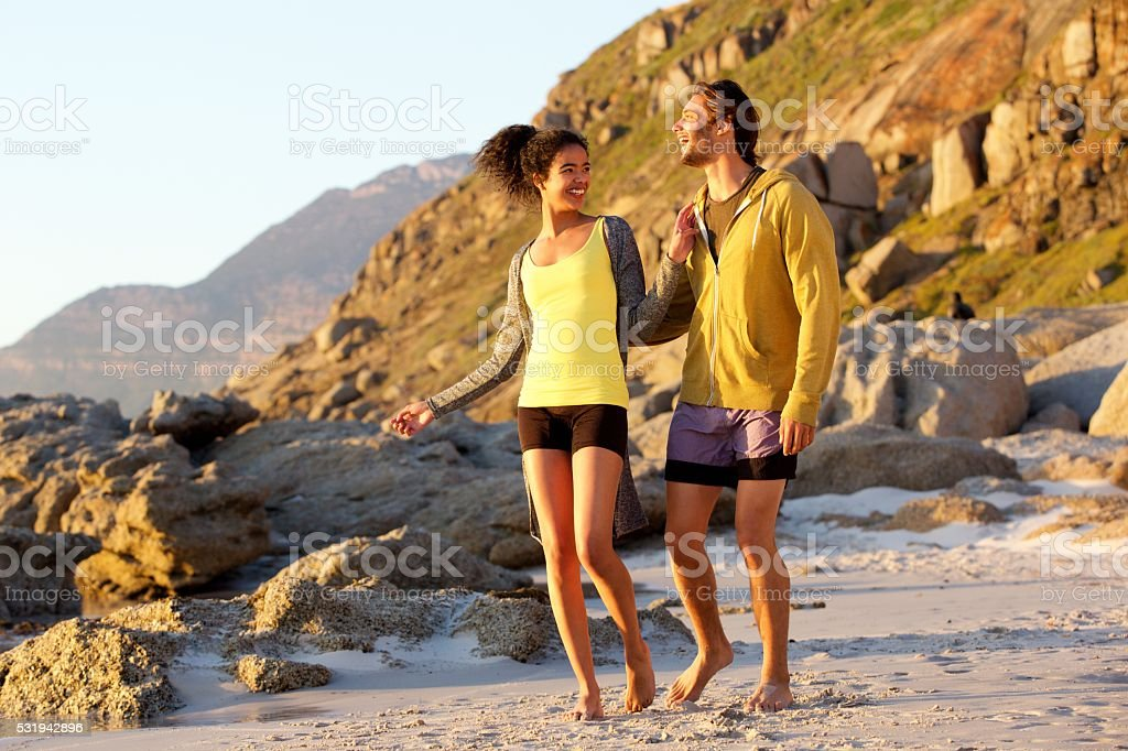 Two friends enjoying a walk on the beach stock photo