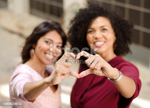 Two attractive mixed race women making a heart shape with their hands in focus