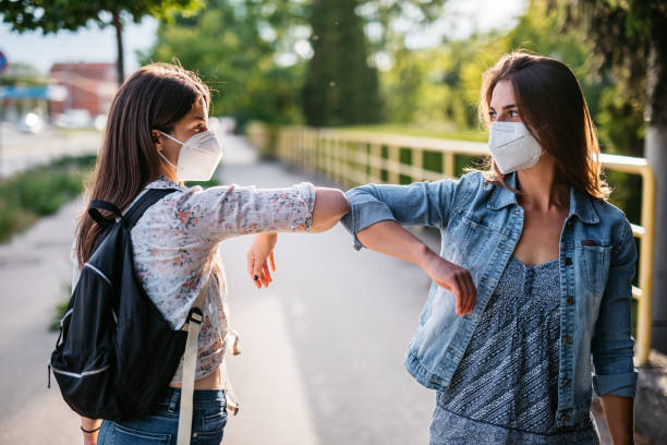 Two friends greeting during pandemic stock photo