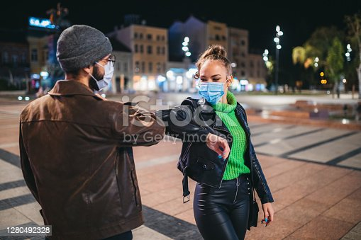 Two young people with protective masks touching their elbows outdoors in the city