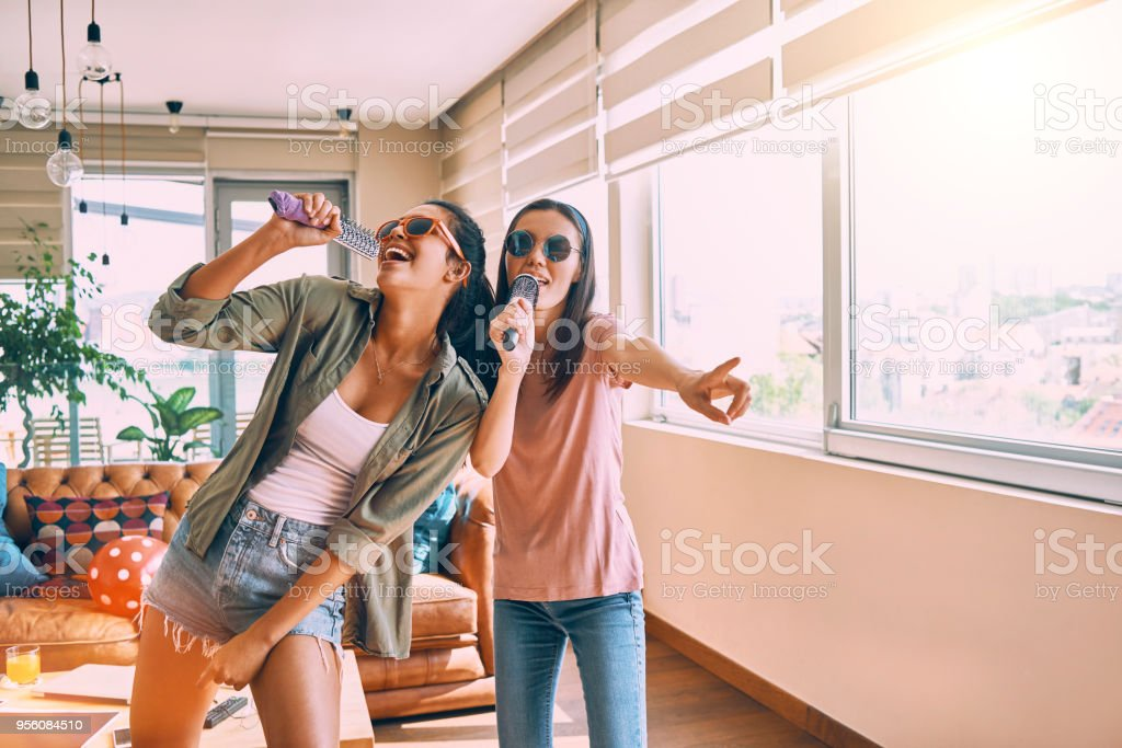 two friends having fun singing together stock photo