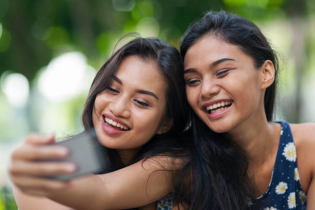 two friends having fun taking a selfie - philippines girl stock photos and pictures