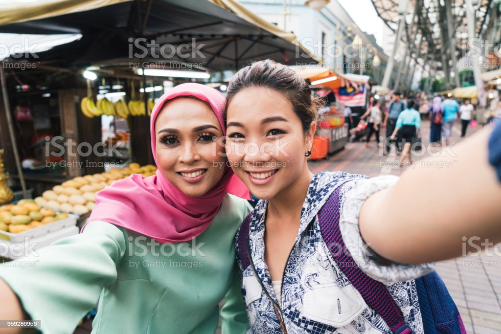 Two friends having selfie together at the market stock photo