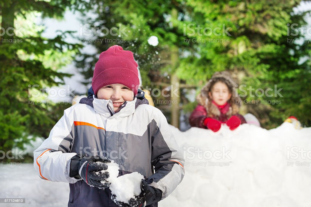Two friends having snowball fight stock photo