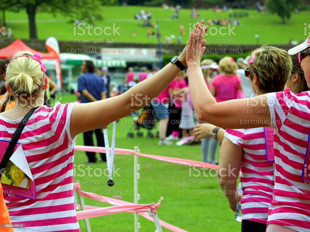 Two friends high fiving at the end of a race. stock photo