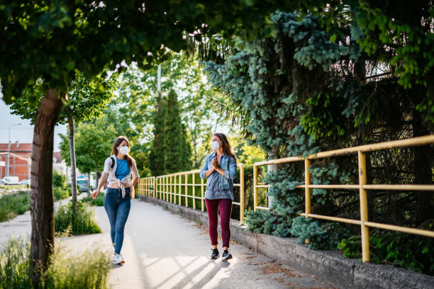 two friends holding social distance during walk - social distancing stock pictures, royalty-free photos & images