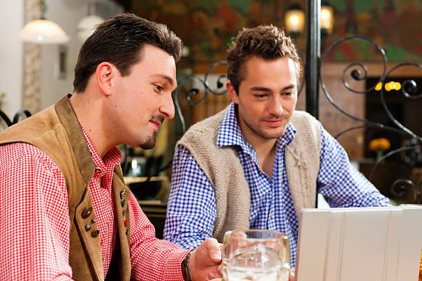 zwei freunde im bayerischen pub mit laptop - top restaurants münchen stock-fotos und bilder
