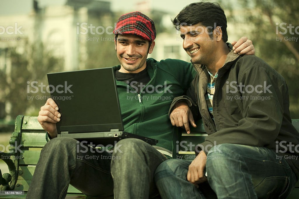 Two friends in park sharing something on a laptop royalty-free stock photo