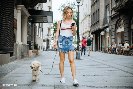Young woman with her dog, enjoy in walk in shaded summer city street