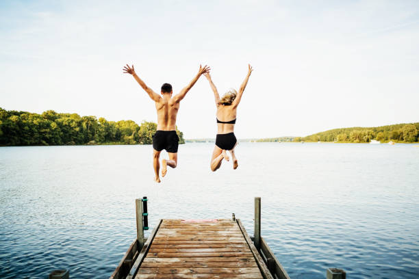 Two Friends Jumping Off Jetty At Lake Together Two friends jumping with their arms in the air off the end of a jetty at a lake together. mid air stock pictures, royalty-free photos & images