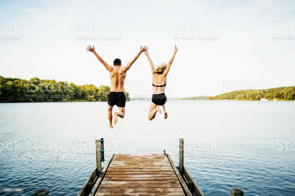 Two Friends Jumping Off Jetty At Lake Together stock photo