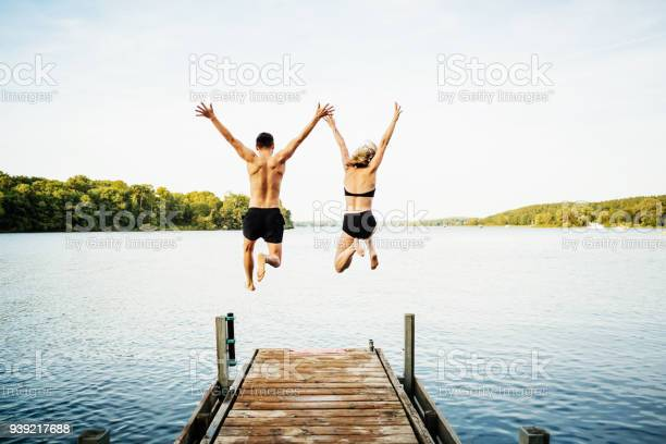 Photo of Two Friends Jumping Off Jetty At Lake Together