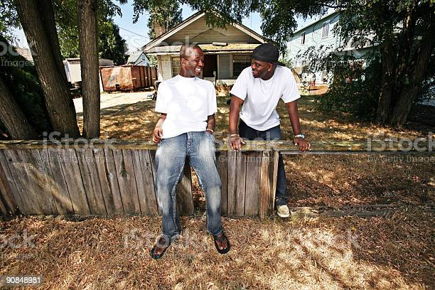 Two Friends Laughing and Leaning on Broken Fence