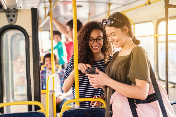 Two friends laughing and watching phone while waiting for bus to depart. Two friends laughing and watching phone while waiting for bus to depart. depart stock pictures, royalty-free photos & images