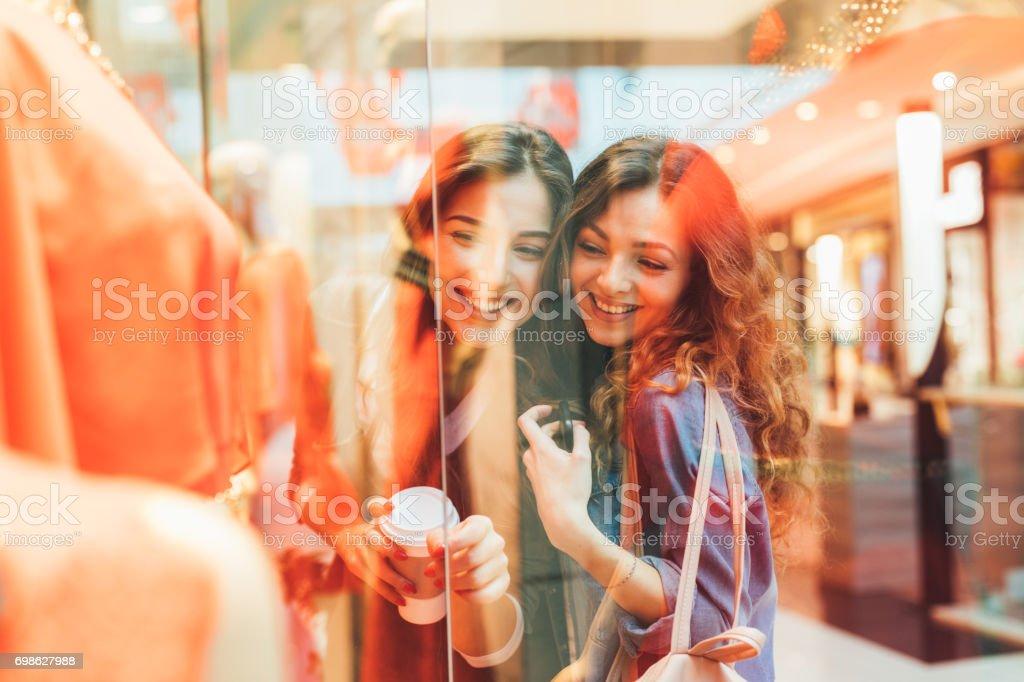 Dois amigos a olhar para um vestido em uma loja de roupas - foto de acervo