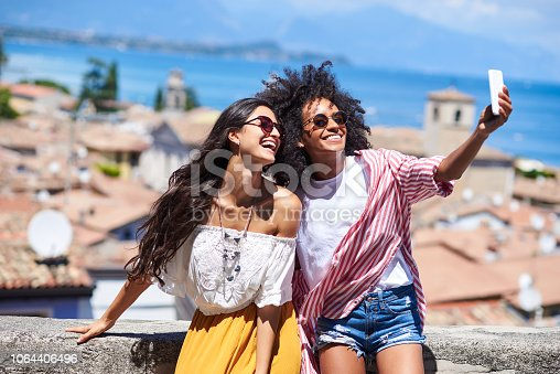Horizontal picture of two girl friends laughing while using mobile phone