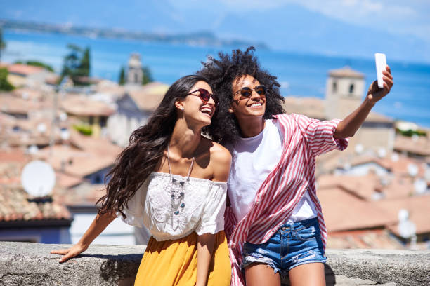 Two friends making a selfie. Horizontal picture of two girl friends laughing while using mobile phone brazilian culture stock pictures, royalty-free photos & images