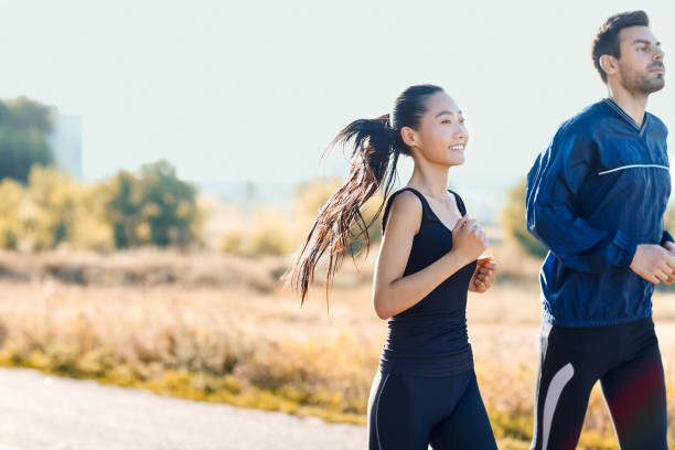 Two friends man and woman jogging on sunny day stock photo