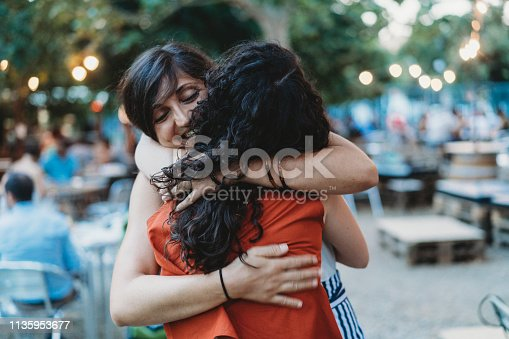 Two friends meeting up, hugging each other