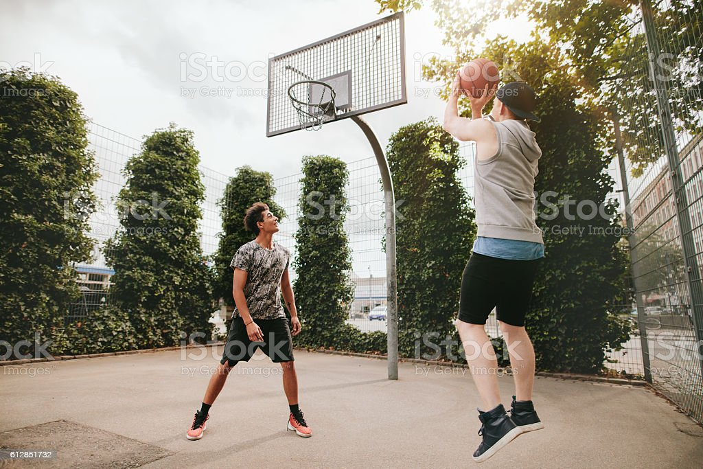 Two friends playing basketball on court stock photo