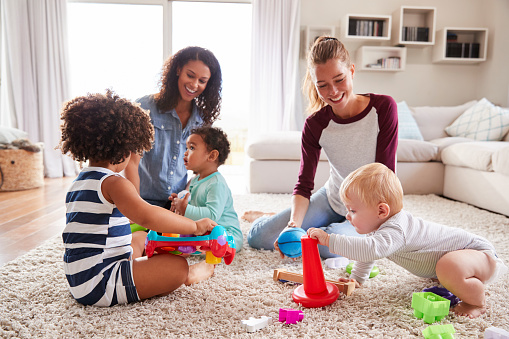 639403466 istock photo Two friends playing with toddler kids on sitting room floor 947850156