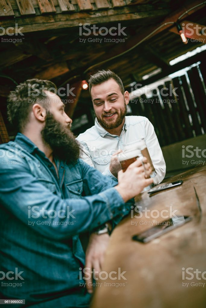 Two Friends Relaxing In Pub After A Hard Days Work stock photo