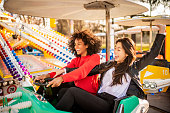 istock Two friends riding amusement park ride 1134778943
